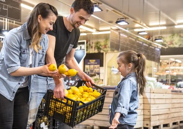 Mãe, marido e filha escolhendo limões no supermercado