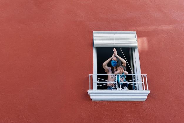 Mãe mascarada batendo palmas da janela com sua filha