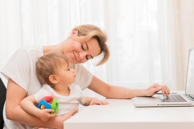 Mãe meados de tiro segurando bebê ficar na mesa e sorrindo