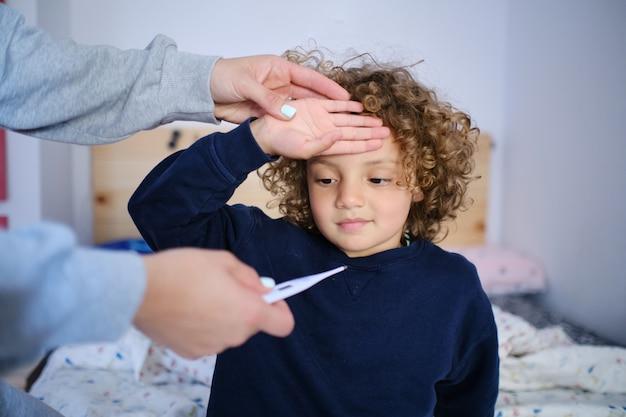 Mãe mede a temperatura de seu filho com sintomas de febre