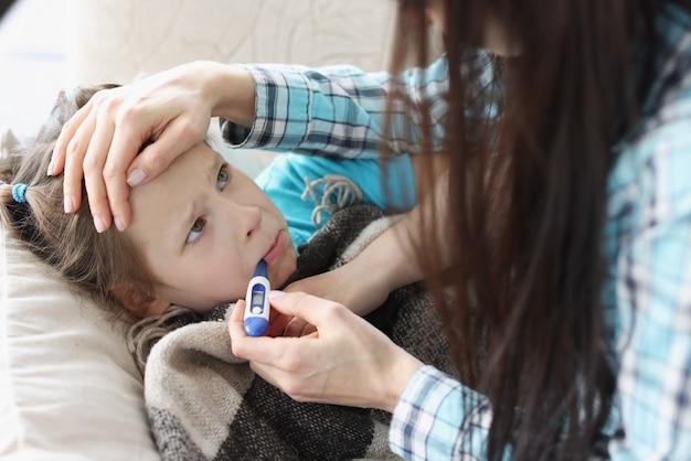 Mãe medindo a temperatura da menina com termômetro na boca