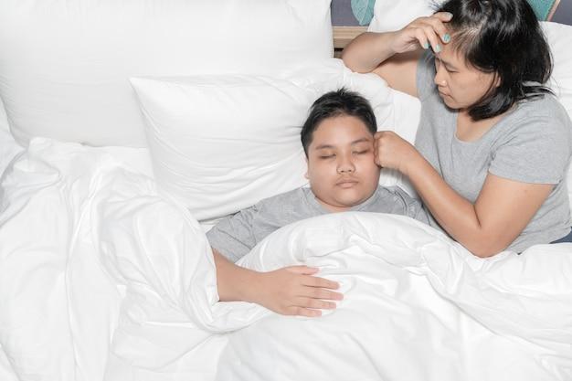 Mãe medindo a temperatura de seu filho doente. criança doente com febre alta deitada na cama e a mãe se sente estressada, conceito de saúde.