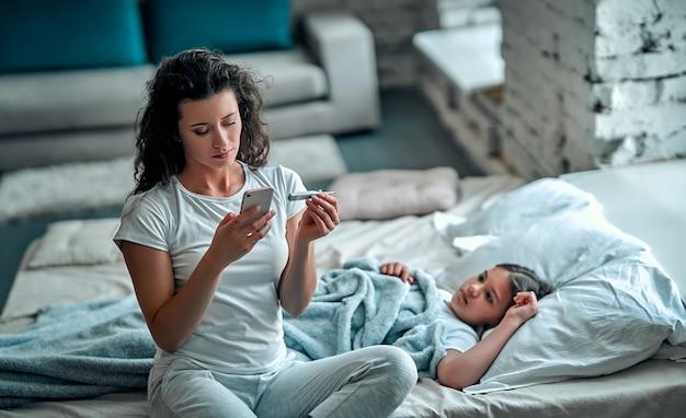 Mãe medindo a temperatura de seu filho doente. criança doente com febre alta deitada na cama e a mãe segurando o termômetro. mãe com celular ligando para o médico