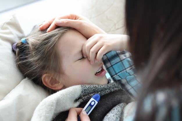 Mãe medindo a temperatura de uma menina doente com termômetro