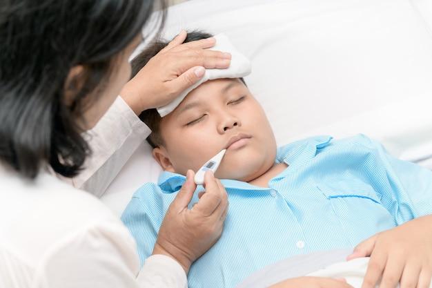Mãe, medindo a temperatura do garoto doente.