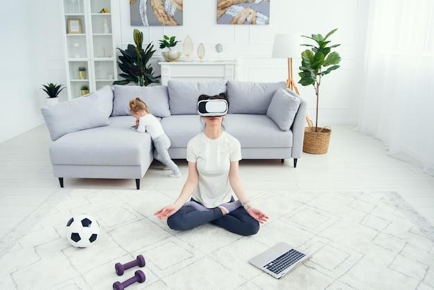 Mãe meditando em posição de ioga de lótus usa óculos de rv enquanto sua filha assiste desenhos no