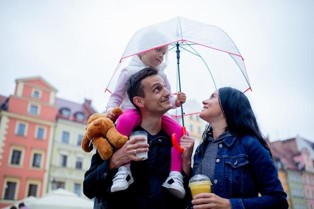 Mãe, menina com guarda-chuva e pai na cidade