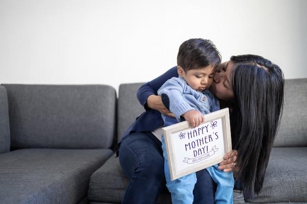 Mãe mexicana beijando filho no dia das mães