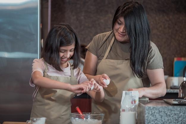 Mãe mexicana e filha cozinhando na cozinha, dia das mães
