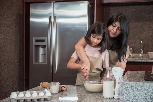 Mãe mexicana ensinando filha a cozinhar na cozinha, dia das mães