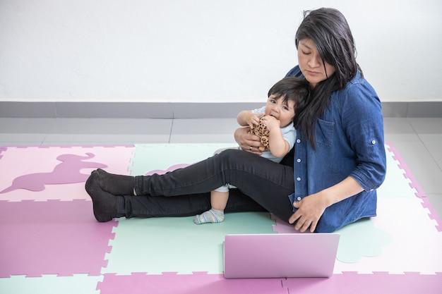 Mãe mexicana, trabalhando em casa, deitado no chão e brincando com o filho