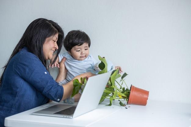 Mãe mexicana trabalhando em casa enquanto o filho a distrai e chama a atenção