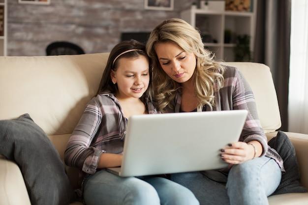 Mãe moderna e filha sentada no sofá em um fim de semana preguiçoso navegando no computador.