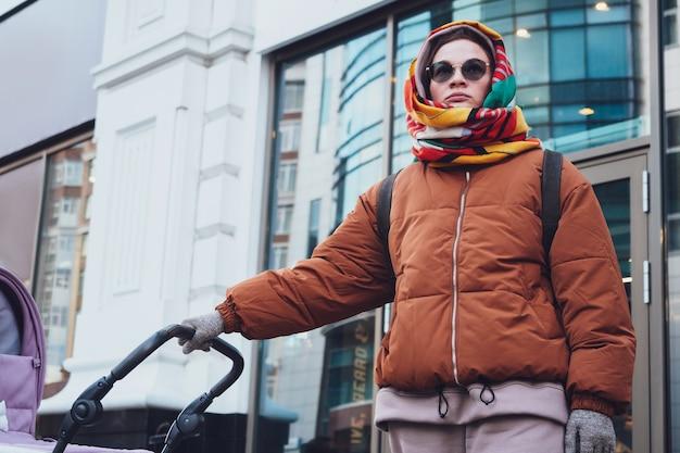 Mãe moderna elegante com um carrinho de criança em uma caminhada na cidade, no outono. mamãe dirige um carrinho pelas ruas, close-up.