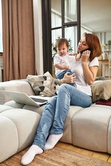 Mãe moderna inventiva com crianças multitarefa de manhã.