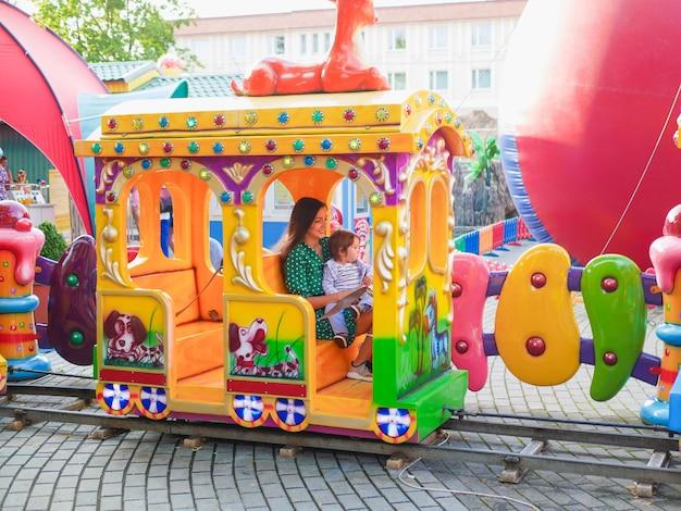 Mãe monta em um trem infantil com uma criança. mãe anda com uma criança em um carrossel. retrato de uma mãe feliz e filho andando em um carrossel