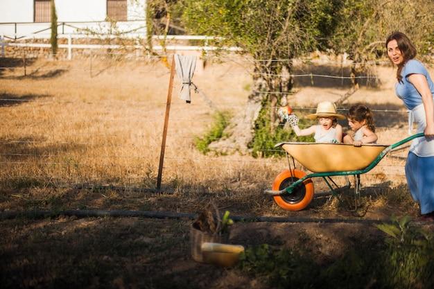 Mãe, montando suas filhas no carrinho de mão