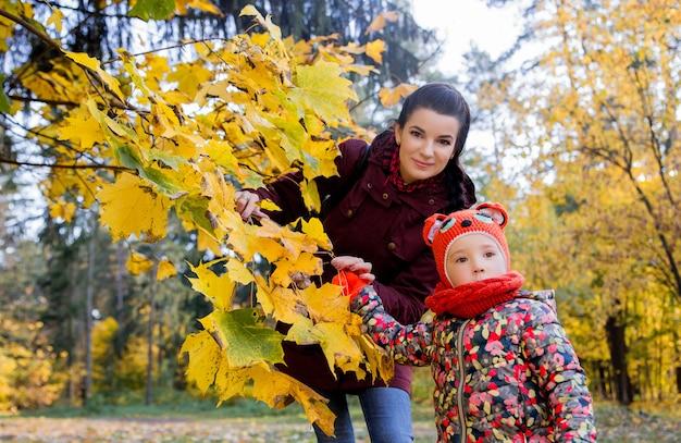 Mãe mostra a filha folhas de outono