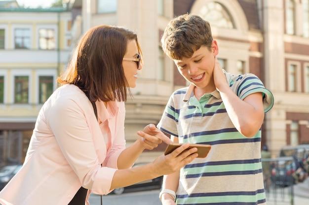 Mãe mostra o filho algo no celular, menino está envergonhado, sorrindo