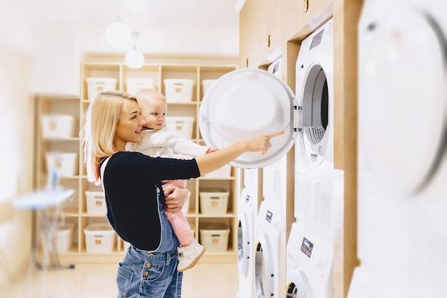 Mãe mostra sua filha uma máquina de lavar roupa