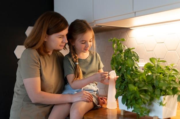 Mãe mostrando à filha como cuidar de uma planta