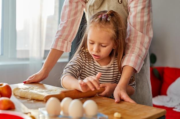 Mãe mostrando à filha como estender a massa para uma torta ou biscoitos, a criança fofa aprendendo muffins proibindo o processo de cozinhar com a mãe feliz na cozinha iluminada