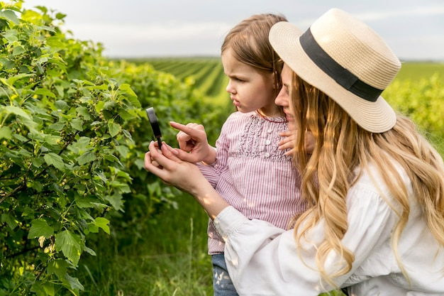 Mãe mostrando plantas para menina