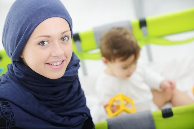 Mãe muçulmana árabe brincando e cuidando de seu bebê