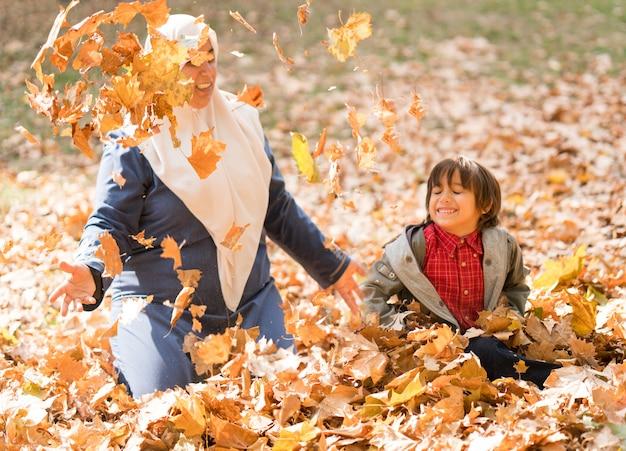 Mãe muçulmana árabe com filho em folhas de outono