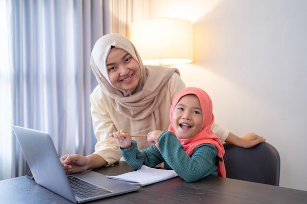 Mãe muçulmana asiática ajuda sua filha a aprender on-line usando um laptop e estudando em casa