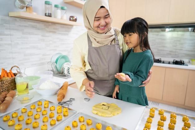 Mãe muçulmana asiática e sua filha fazendo um bolo de nastar juntas em casa na cozinha
