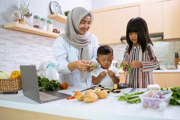 Mãe muçulmana assistindo a um vídeo de culinária no laptop e fazendo o jantar com seus dois filhos na cozinha juntos