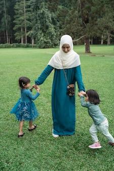 Mãe muçulmana brinca com seus dois filhos