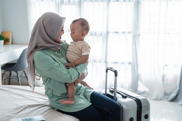 Mãe muçulmana carregando seu bebê enquanto está sentado na cama