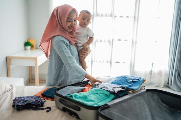 Mãe muçulmana carregando seu filho enquanto prepara a mala