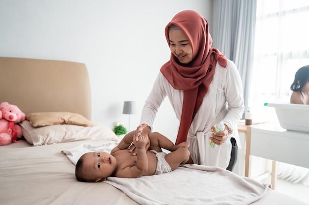 Mãe muçulmana dando massagem para seu bebê