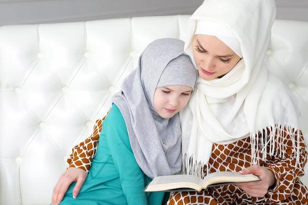 Mãe muçulmana em hijab branco e roupas tradicionais está lendo um livro para sua filha e aninhando-a sentada no sofá em casa em um interior moderno branco.