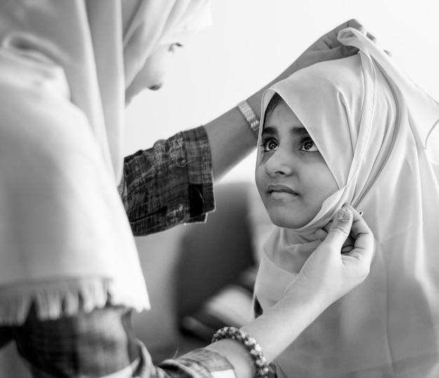 Mãe muçulmana ensinando filha a usar um hijab
