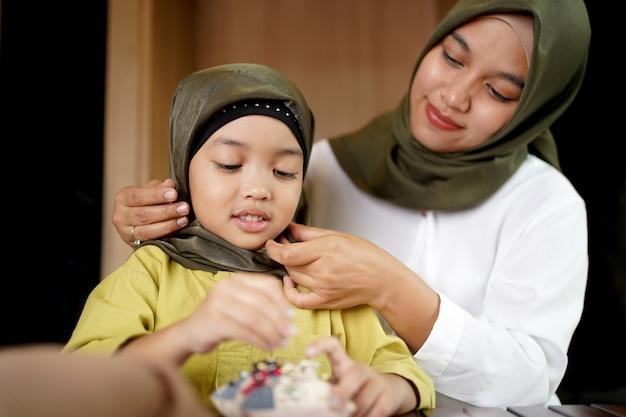 Mãe muçulmana ensinando sua filha a usar um hijab.