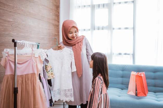 Mãe muçulmana escolhendo um vestido para sua filha em uma loja de roupas