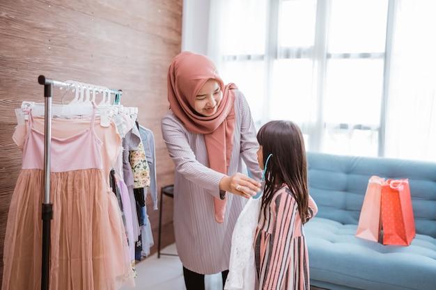 Mãe muçulmana fazendo compras com a filha em uma butique de roupas
