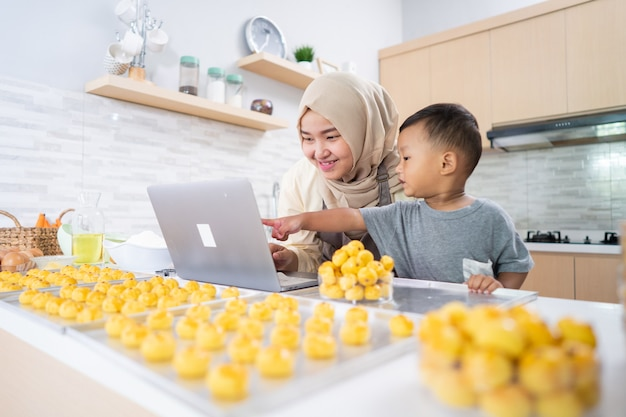 Mãe muçulmana olhando para o laptop enquanto faz bolo com o filho na cozinha. bolo de nastar