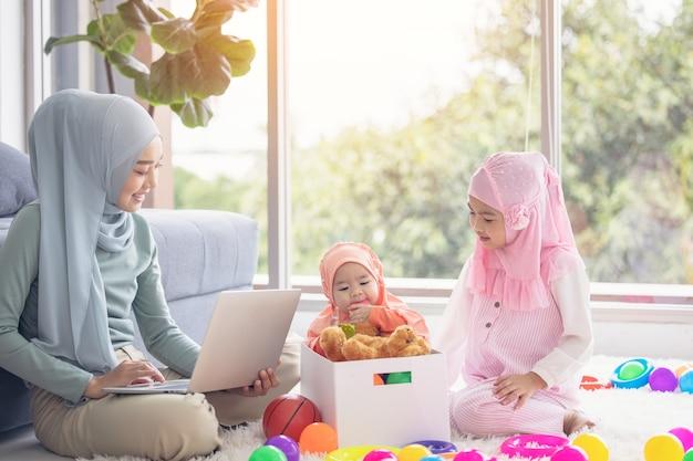 Mãe muçulmana trabalhando com laptop e bebezinho brincando de brinquedos na sala de estar em casa.