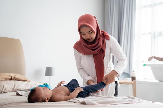 Mãe mudar sua fralda de bebê menino
