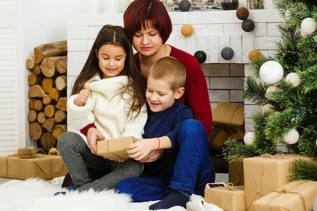 Mãe muito jovem com sua filha bonita e filho perto de árvore de natal