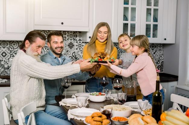 Mãe muito jovem com uma deliciosa turquia para o jantar de férias com a família