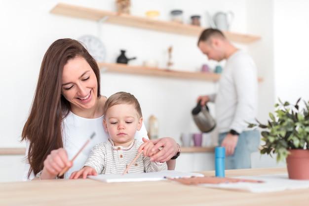 Mãe na cozinha com criança e pai desfocado