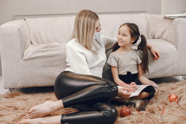 Mãe na máscara com a filha no chão. colorir menina e mãe ajudando-a.
