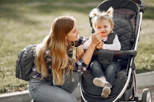 Mãe na rua da cidade. mulher com seu filho sentado em um carrinho de bebê. conceito de família.