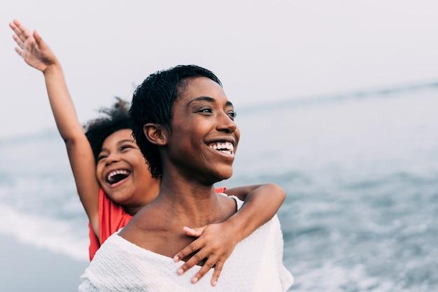 Mãe negra e filha correndo na praia ao pôr do sol